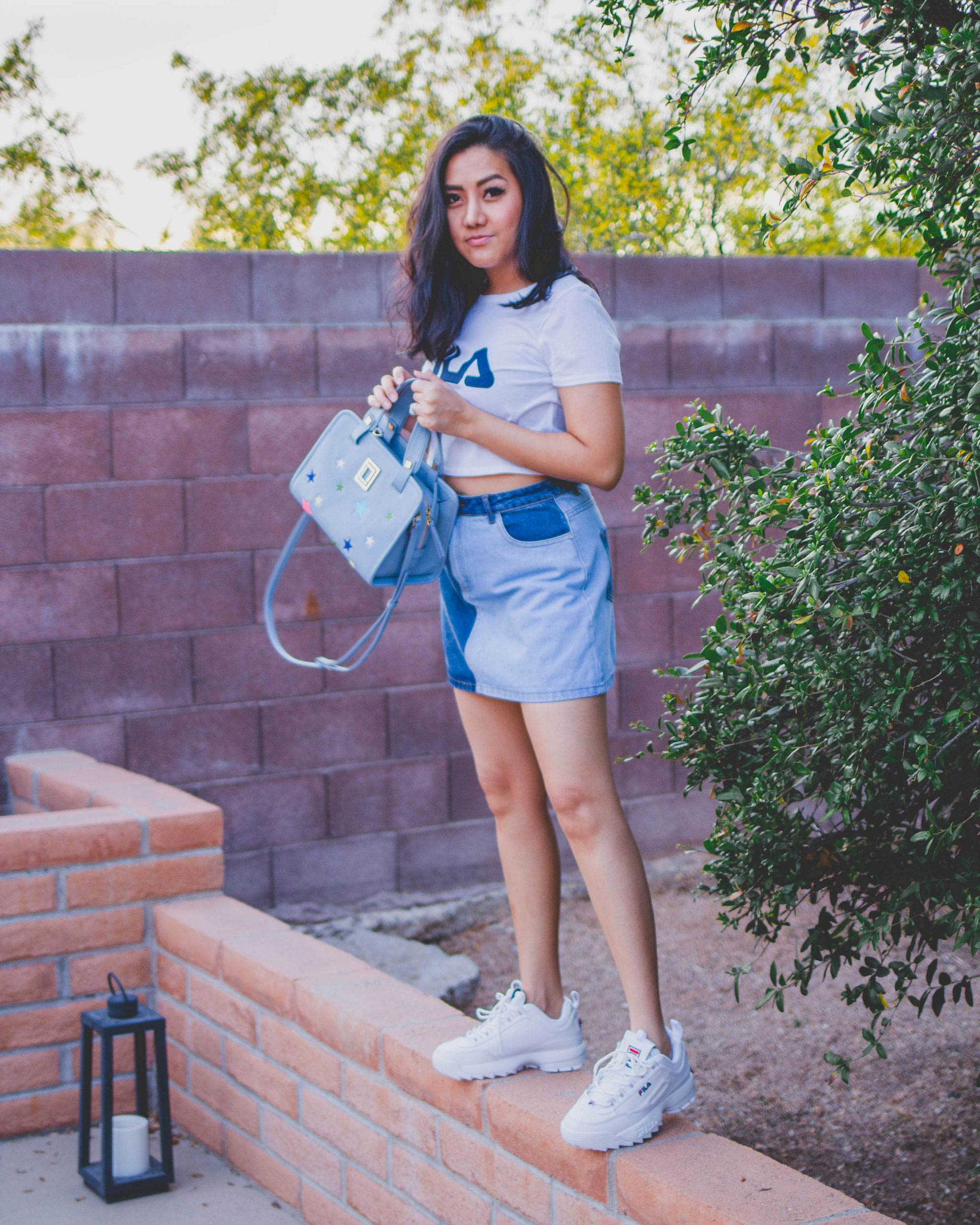 Arizona Fashion blogger Molly Larsen Wearing white FILA Logo crop top tee with blue denim mini skirt